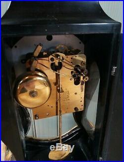 Une ancienne pendule en bois laqué noir avec dorure